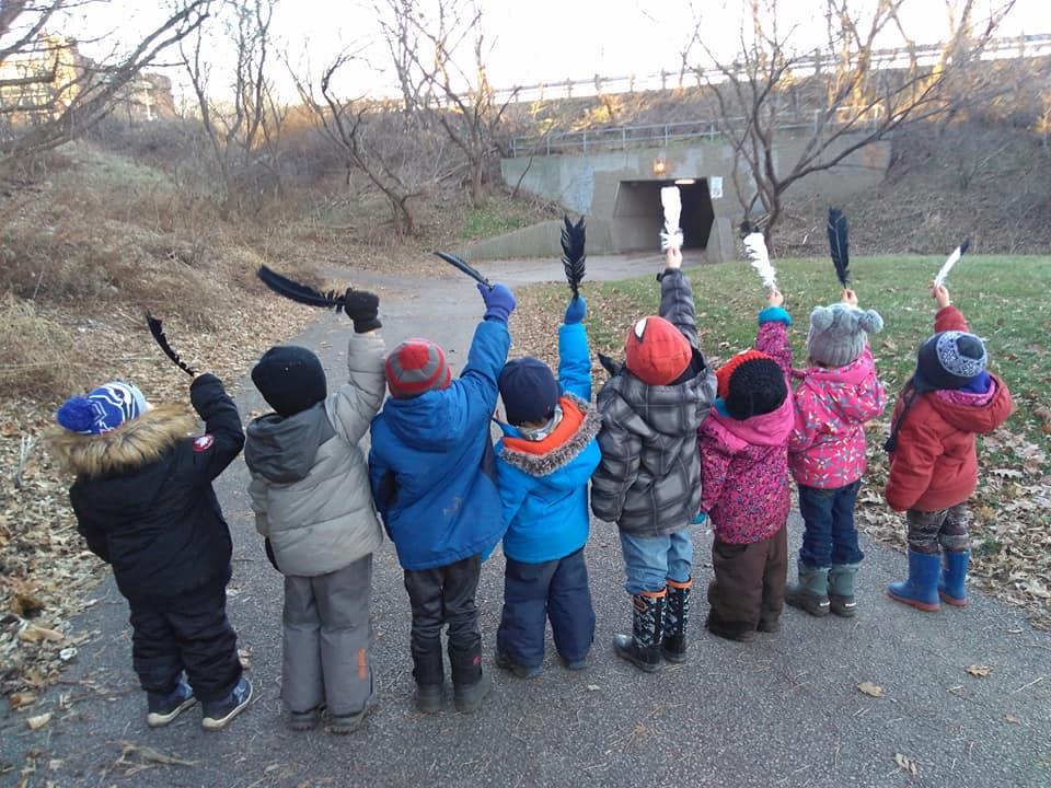 children raising up feathers in their hands on a trail