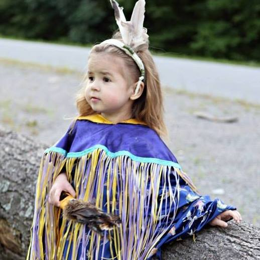 young girl in regalia leaning touching a tree trunk